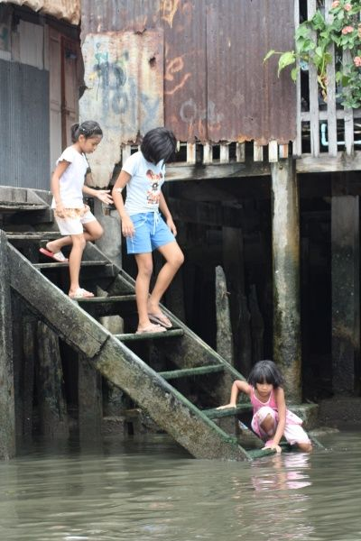 On a river ride round Bangkok, these young residence made their way down the stairs to their water garden